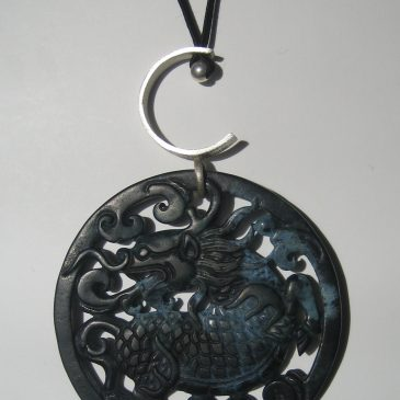 281-1214 Col·Silver Collection. Black jade pendant, 70mm dia, cut on both sides, argent i soutage negra
