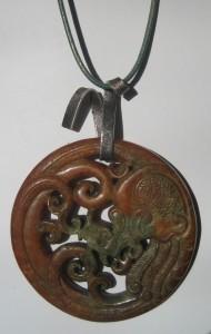 283-1214 Penjoll de jade marró-verd, 70mm dià, tallat a dues cares, argent i cuir verd