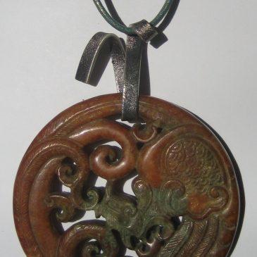 283-1214 Col·lecció Argent. Penjoll de jade marró-verd, 70mm dià, tallat a dues cares, argent i cuir verd